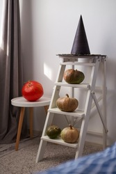 Preparing for Halloween: Decorating the room with orange pumpkins and a handmade witch hat. Selective focus