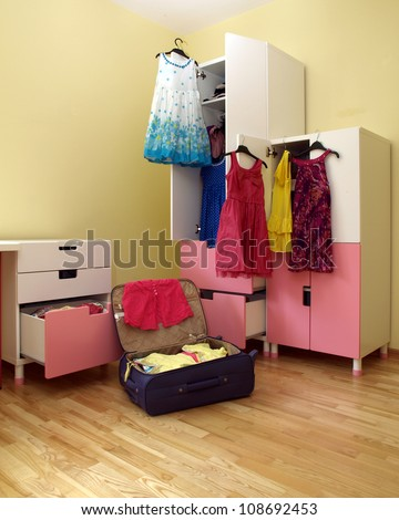 Preparing for holiday, packing girl\'s suitcase