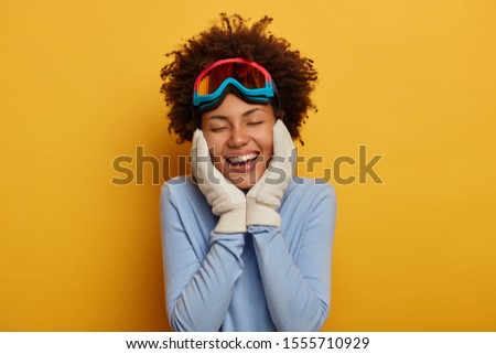 Preparing for winter. Joyful curly young woman in snowboard wear, keeps both hands on cheeks, wears warm gloves, recalls pleasant moment of vacation, models over yellow wall. Sport and hobby