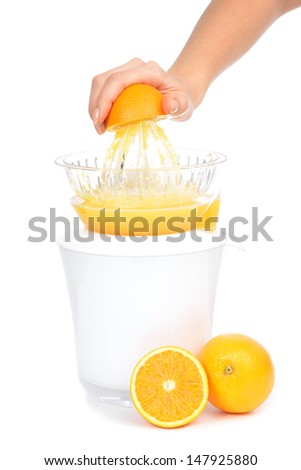 Preparing fresh orange juice squeezed with electric juicer on a white background