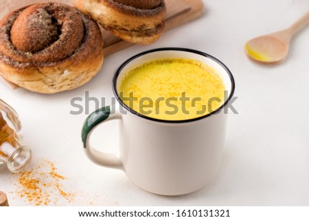 preparing indian drink golden milk on a white background. nearby spiced spices and breakfast roll