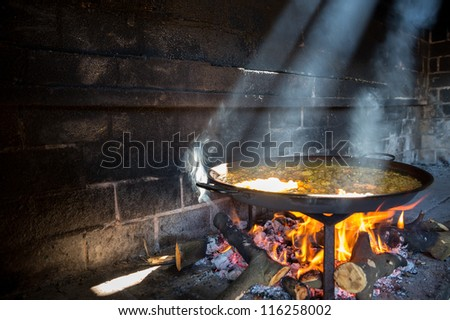preparing large dish of paella with firewood