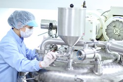 Preparing machine for work in pharmaceutical factory. Chemical industry. Pharmaceutical Factory Worker. Pharmaceutical Industry.