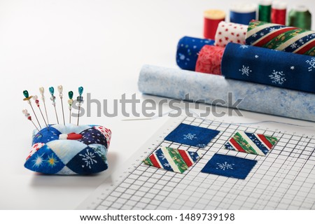Preparing of square pieces of fabrics for sewing quilt on craft mat, pincushion, fabric rolls, spools of thread #1489739198
