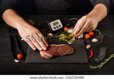 preparing rare beef steak olive oil on a dark background #526336480