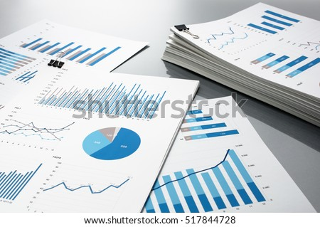 Preparing report. Blue graphs and charts. Business reports and pile of documents on gray reflection background.