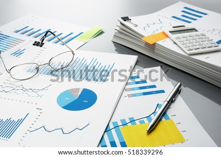 Preparing report. Blue graphs, glasses, calculator and pen. Business reports and pile of documents on gray reflection background.