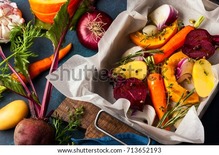 Preparing  roasted vegetables with garlic and herbs on the baking tray. Autumn-winter root vegetables. #713652193