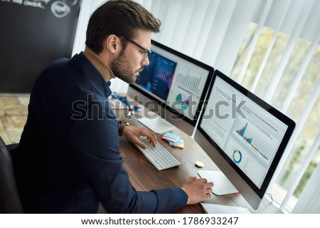 Preparing statistical report. Focused businessman or financial analyst working in the modern office, looking at graphs and charts on computer and analyzing statistical data. Business, finance, sales