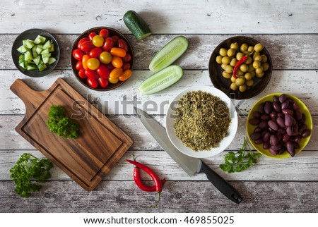Preparing Tabbouleh, tabouleh salad with vege meatballs, pita bread and olives, a refreshing mediterranean salad made with mint, parsley and lemon, on white wooden table, rustic style - Shutterstock ID 469855025