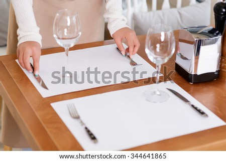 Preparing tables. Attractive waitress is putting silverware on the table for her future customers.