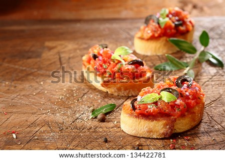 Preparing tasty Italian bruschetta with chopped vegetables and oil on grilled or toasted crusty baguette sprinkled with seasoning and spices on an old grungy scored wooden chopping board