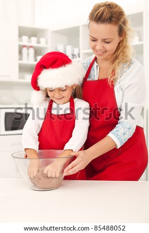 Preparing the christmas cookie dough - happy girls in the kitchen - stock photo