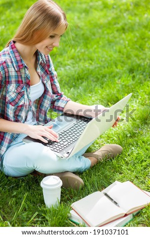 Preparing to exams outdoors. Beautiful young female student working on laptop and smiling while sitting in a park with books around her