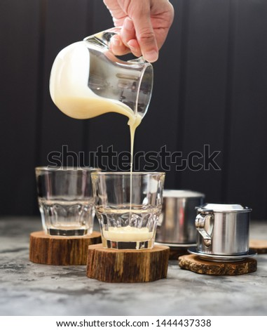 Preparing Vietnamese pour over coffee. Woman hand pouring condensed milk into glasses on dark background copy space #1444437338