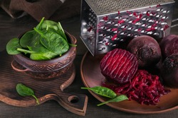 Prepearing beetroot salad on dark wooden background. Cooked beets and baby spinach leaves in clay bowl