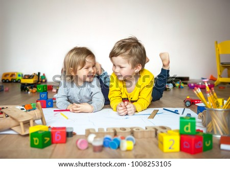 Preschool boy and girl play on floor with educational toys - blocks, train, railroad, plane. Toddler kids drawing. Toys for preschool and kindergarten. Children at  home or daycare. Top view