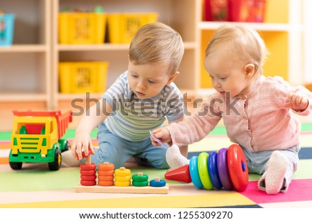 Preschool boy and girl playing on floor with educational toys. Children toddlers at home or daycare. #1255309270