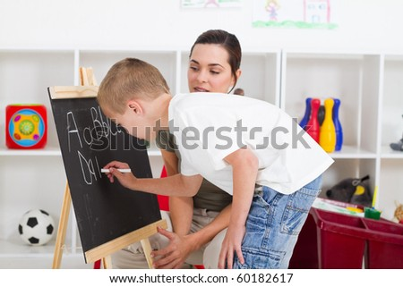 preschool boy and teacher in front of black board in classroom