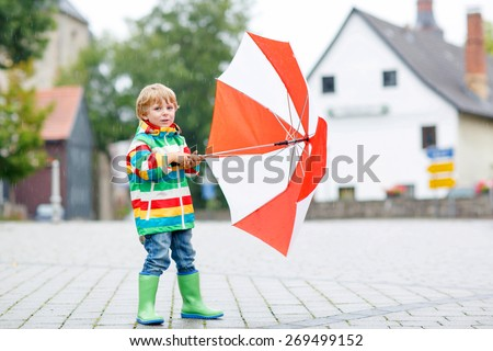 Preschool boy in waterproof clothes and boots walking on the street of a small town on rainy day.
