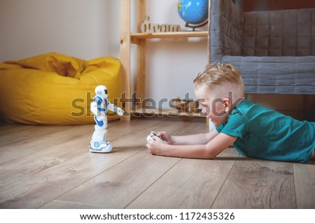 Preschool  boy playing with toy robot at home or daycare. Toys for preschool and kindergarten.  Educational toys for boy and girl. Educational lessons and programming Stock photo ©