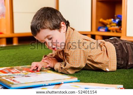 Preschool boy reading a large book - stock photo