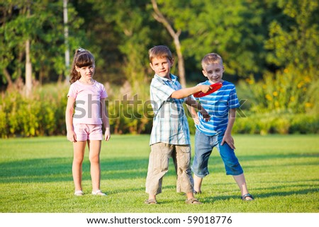 Preschool boy throwing frisbie, his friends looking beside