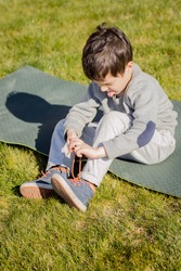 Preschool child trying to tie a lace on his boot himself. Trying hard. Stuck out his tongue. Sits on mat on green grass. Concept of self-activity, skills, children's age, learning to dress, self-care.