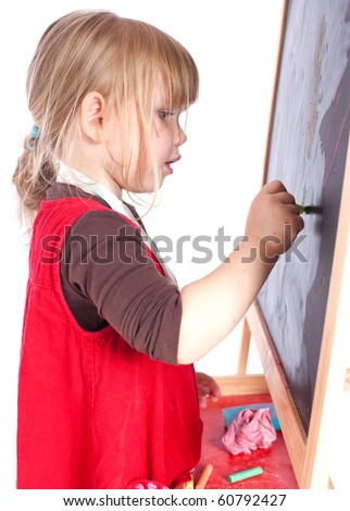 preschool girl in red dress drawing on blackboard