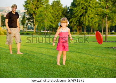 Preschool girl throwing frisbie - stock photo