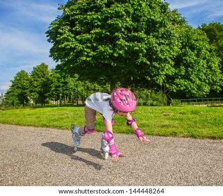 Preschool girl with inline roller skates on, falling down #144448264
