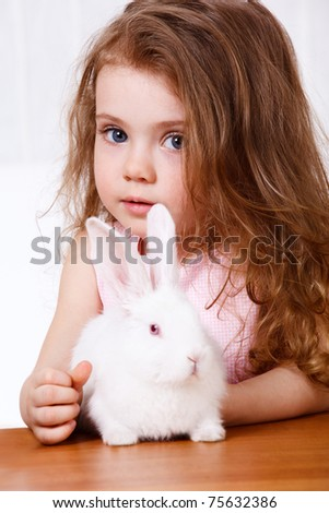 Preschool girl with long hair and a white rabbit sitting on the table