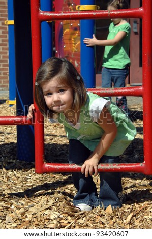 Preschool morning break includes exercise time on the playground equipment.  Little girl climbs through metal ladder.  Wood chips cover ground for safety.