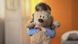 Preschool shy girl hiding behind teddy bear, childish psychological problems