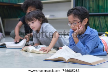 Preschool students laying on floor and rest the chin on the hand, read the book in library, Learning and education concept. #746685283