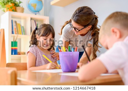 Preschool teacher looking at smart child learning to write and draw. Early education. Harnessing creativity and support. Stock foto ©