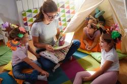 Preschool teacher reading a story to children at kindergarten. Mother reading to the children.