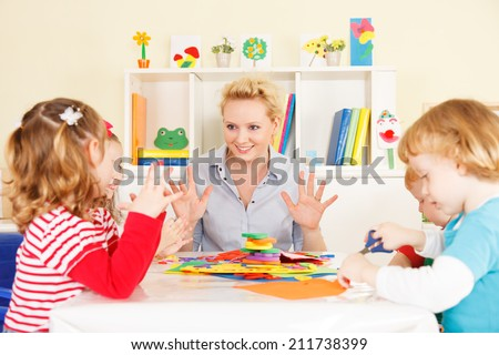 Preschool: Young smiling teacher discussing with group of children. Learning and having fun. Selective focus to teacher talking.