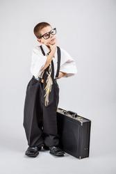 Preschooler boy in an adult business suit thinking
