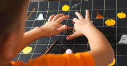 Preschooler boy making board game field for Halloween game, child sticks a drawing of a black cat