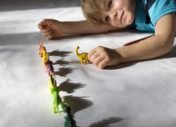 preschooler boy playing with shadows from toy dinosaurs standing in row. creative ideas for children's entertainment at home. Passion for paleontology. contrasting shadows and light. Selective focus.
