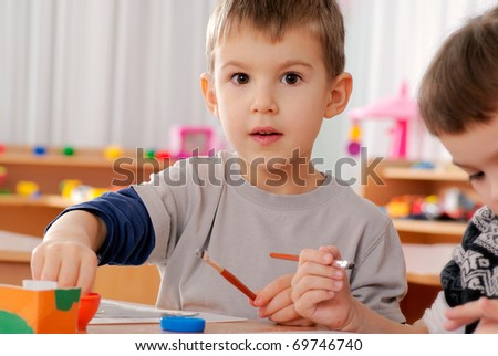 preschooler boy 4 years old drawing in classroom