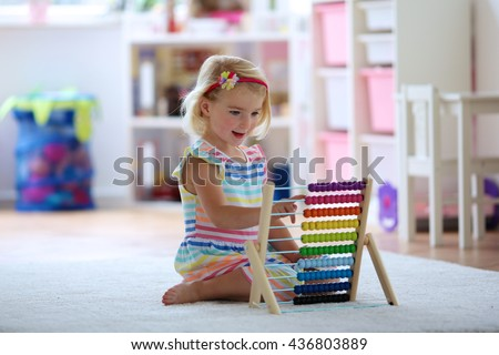 Preschooler girl learns to count. Cute child playing with abacus. Little girl having fun indoors at home, kindergarten or day care centre Educational concept for school kids.
