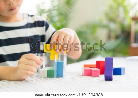 Preschooler plays colorful block puzzle. Child development - Hands-on activities developing problem solving skill, cognitive skill, concentration and emotional intelligence. Learn through play. #1391304368