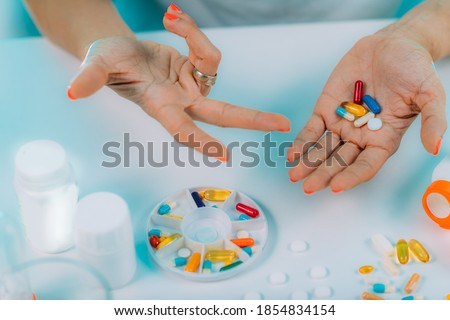 Prescribed medication non-adherence. Female patient counting pills.  Stock photo ©