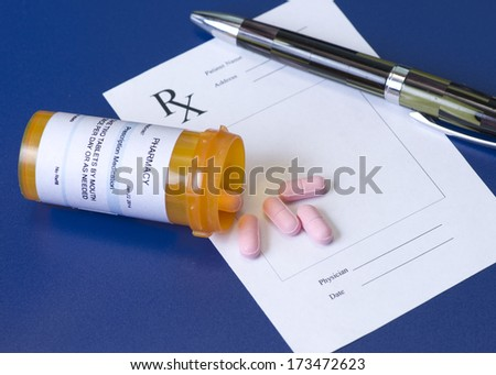 Prescription bottle, pink pills, pen, and pad on royal blue background.