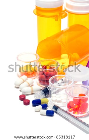 Prescription medicine pills and sample medication drug tablets in high dosage with syringes and pharmaceutical amber bottles for an aggressive medical treatment regimen to treat and cure a disease