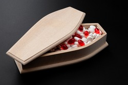 Prescription pharmaceutical drugs and deadly pill addiction as sickness concept with wooden coffin full of generic red gel capsules and white pills isolated on black background