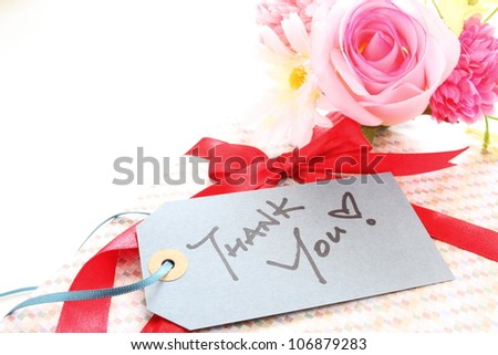 Present and bouquet with thank you Card in handwriting