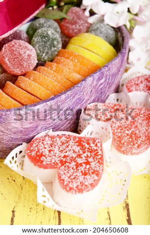 Present box with sweets and flowers on wooden background